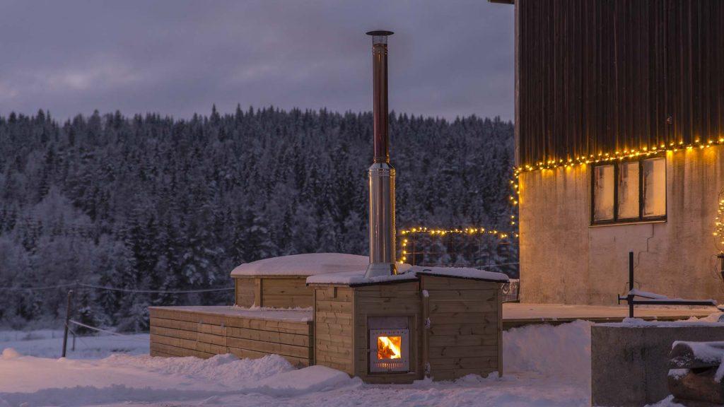 Spabad med kamin utomhus i vinterskrud